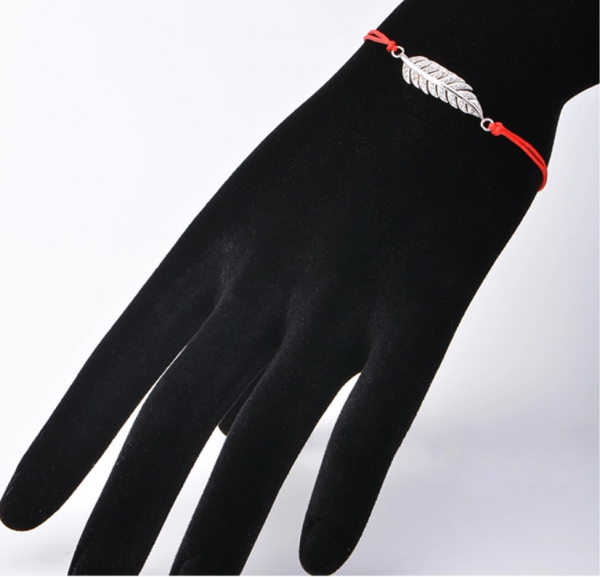 The bracelet is on the arm of a mannequin with a focus on the silver element.