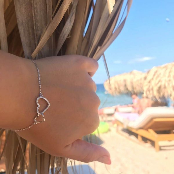 сребърна гривна две сърца едно цяло снимана в созопол на женска ръка