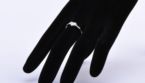 """Silver """"Love"""" ring with cubic zirconia on the hand of a mannequin"""