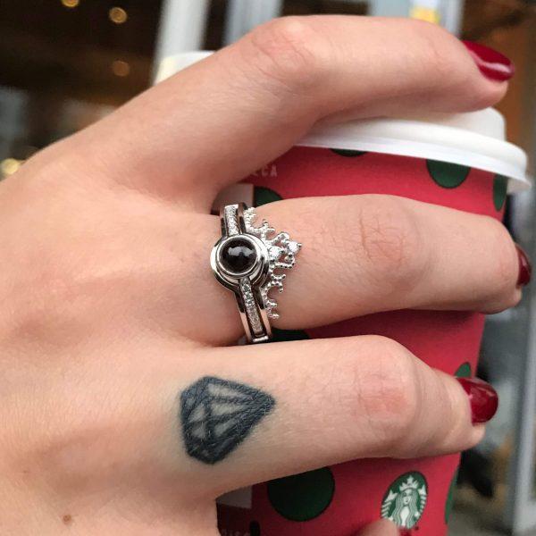 сребърен пръстен безгранична любов обичма те на 100 езика сниман върху женска ръка която държи червена чаша на старбъкс и татуриовка диамант на пръста