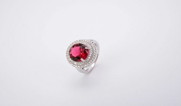 silver ring with cubic zirconia and red stone photographed on the right