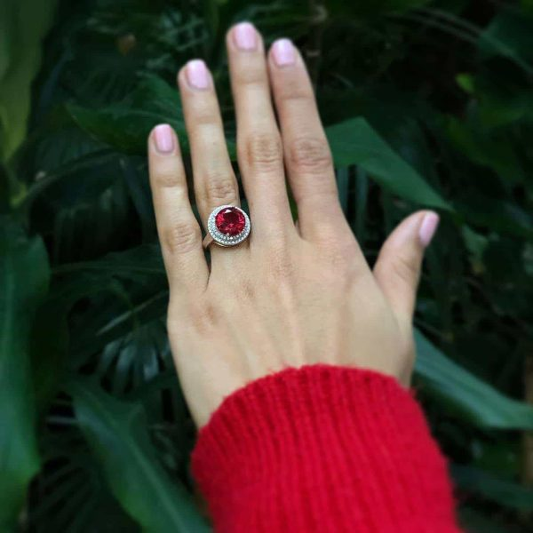 silver royal ring with cubic zirconia and large red stone on a woman's hand