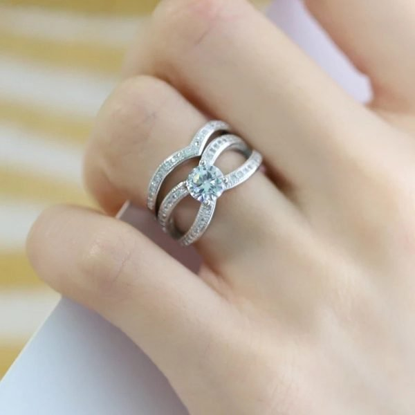 double silver ring with a large stone and small cubic zirconia stones photographed on a woman's hand