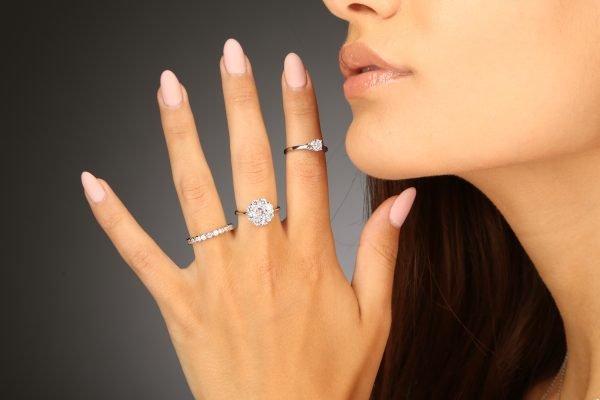 Детайлна снимка на дамска ръка с три сребърни пръстена обсипани с кубични циркони