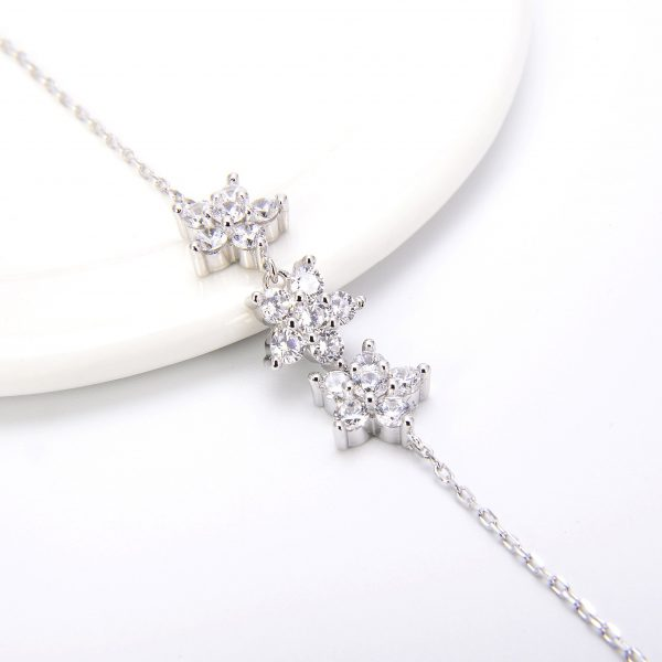 Focus on silver pendants in the shape of flowers made of cubic zircons