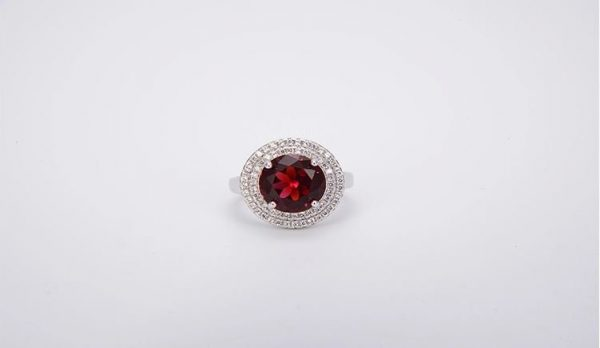 silver ring with a red cubic zirconia stone photographed frontally to the side