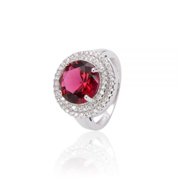 silver ring with red cubic zirconia stone photographed frontally