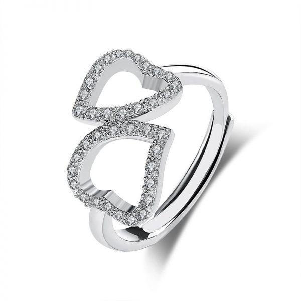 саморегулиращ сребърен пръстен с две сърца и кубичен цирконий сниман централно на бял фон