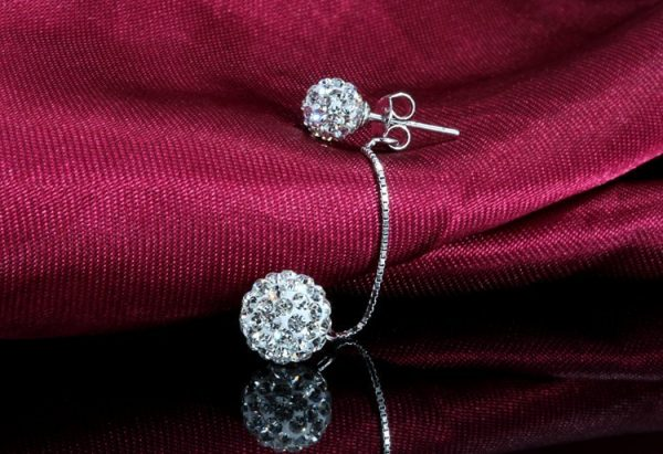 hanging silver earring with cubic zirconia stones photographed on red background