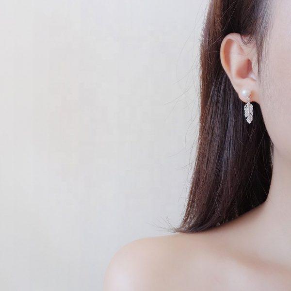сребърни обеци с перла във формата на листо снимани на женско ухо