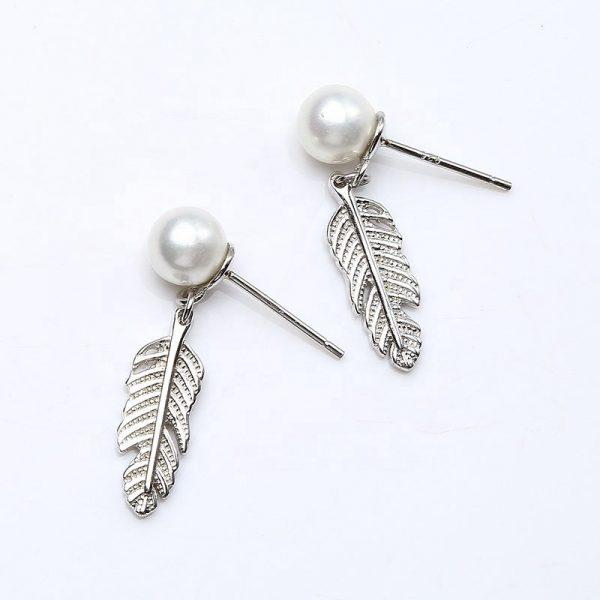 сребърни обеци във формата на листо с перла на върха снимани на бял фон