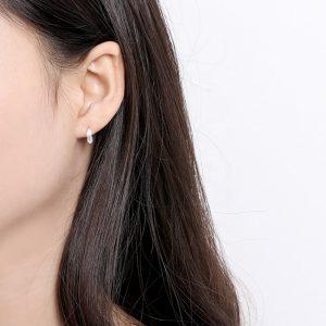 кръгли сребърни обеци с листо по средата снимани на женско ухо