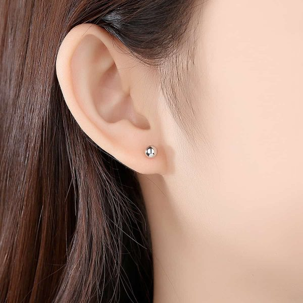 woman with simple pattern round silver screw earrings