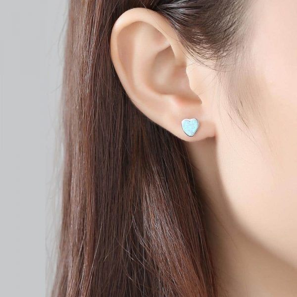 ladies ear with silver earring on a screw in the shape of a heart with a light synthetic opal