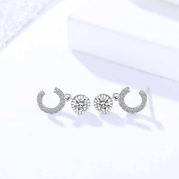 silver earrings with cubic zirconia stone in the shape of the letter C photographed sideways