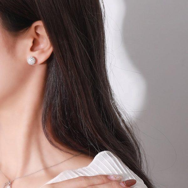 women's silver stud earrings with cubic zirconia on a woman's ear