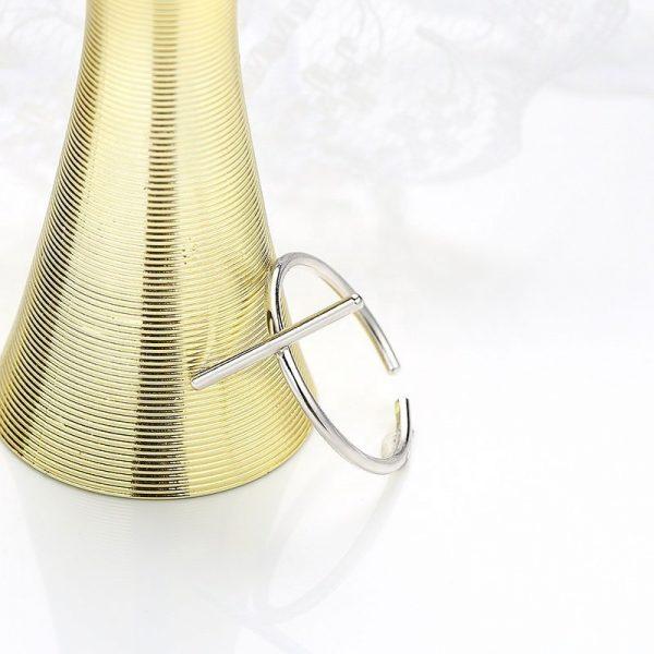 саморегулиращ сребърен пръстен във формата на кръст облегнат на златна ваза