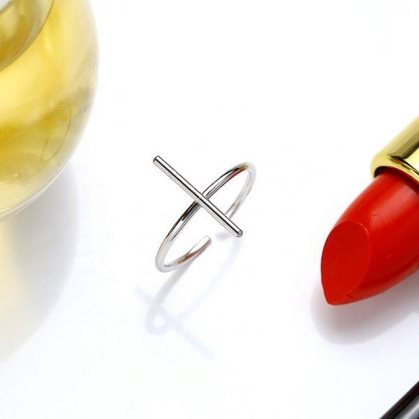 саморегулиращ сребърен пръстен във формата на кръст до златна ваза и червено червило