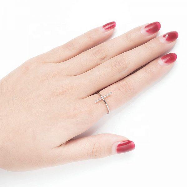 саморегулиращ сребърен пръстен във формата на кръст на женска ръка с червен лак на ноктите