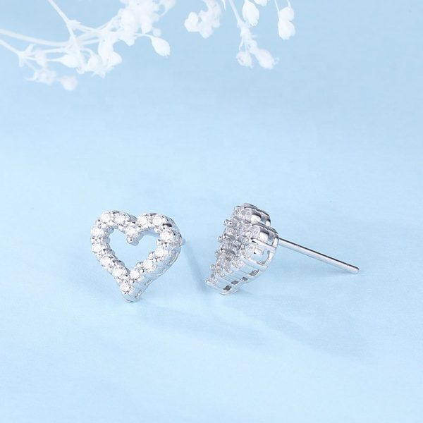silver earrings in the shape of a heart and cubic zirconia stones on a blue background at an angle