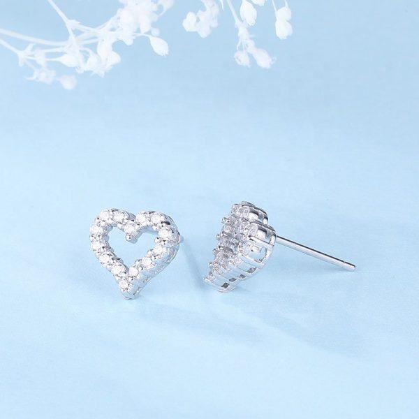 сребърни обеци във формата на сърце и камъни от кубичен цирконий на син фон под ъгъл