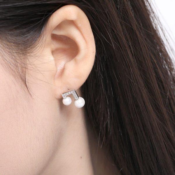 сребърни обеци с кубичен цирконий и две перли на женско ухо на жена с черна коса