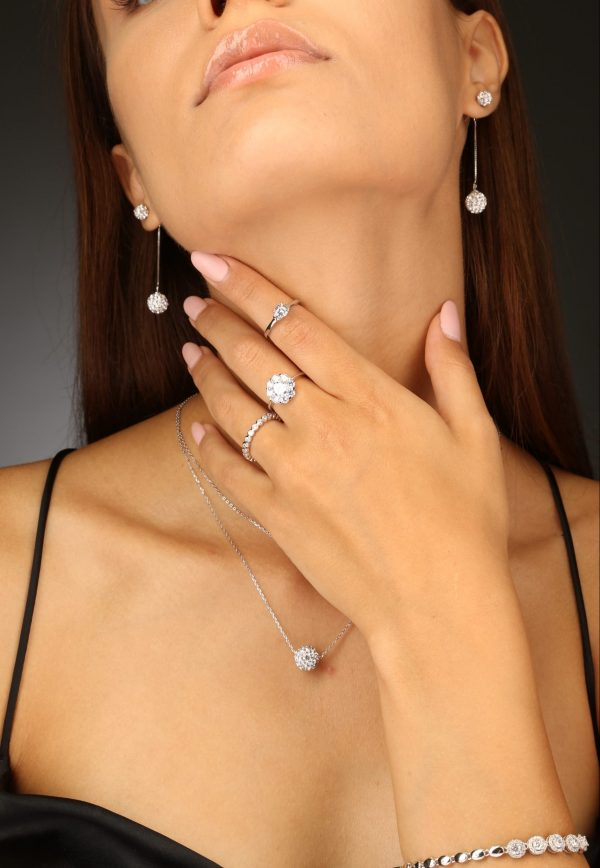 frontal shot of a female model wearing three silver rings, a pair of earrings and a bracelet covered with cubic zircons