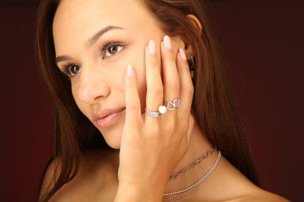 Странична снимка от близък план на модел носещ редица сребърни бижута, като фокосът е върху два сребърни пръстена с кубичен цирконий