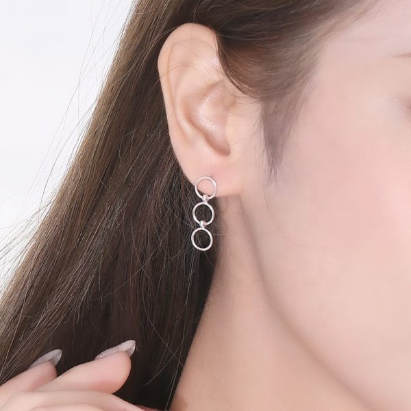 тройни висящи сребърни обеци във формата на кръгове снимани върху женско ухо под ъгъл