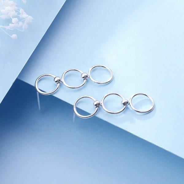 кръгли сребърни обеци с проба на среброто 925 снимани настрани на син фон
