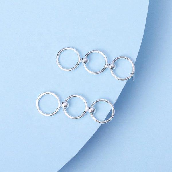 тройни висящи сребърни обеци снимани на син фон във формата на три кръга