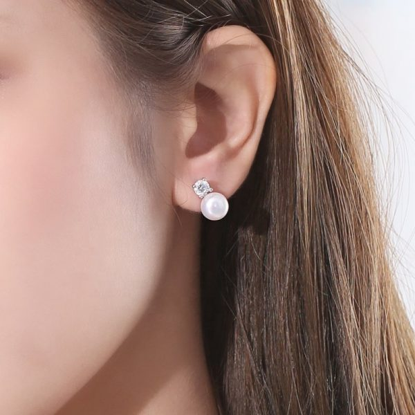 silver earrings with cubic zirconia and pearl on female ear