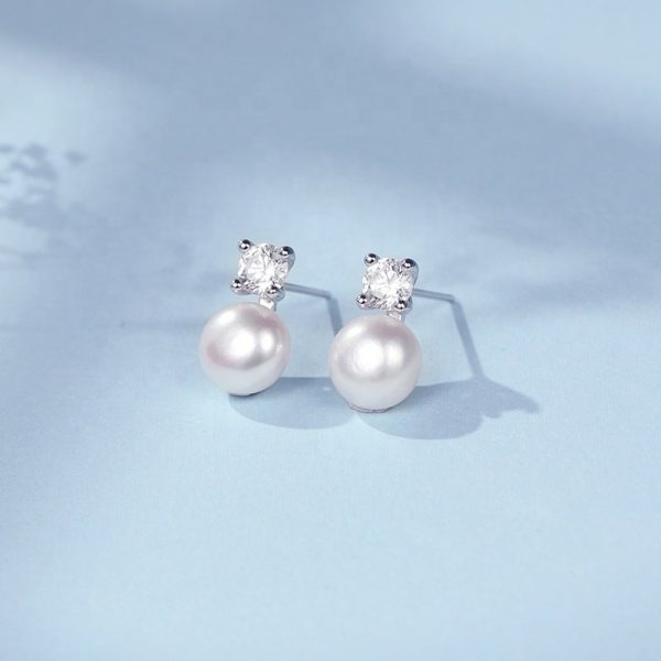 silver earrings with cubic zirconia and pearl at an angle