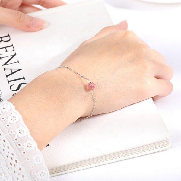 сребърна гривна с розов кристал на женска ръка на фона на бяла книга