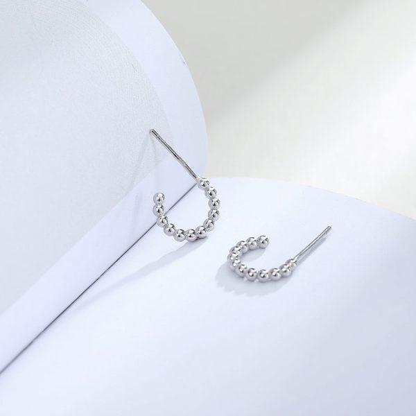 сребърни обеци с топчета върху разгърната бяла книга
