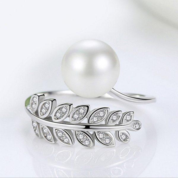 сребърен саморегулиращ пръстен във формата на листо с камъни от кубичен цирконий и перла сниман централно от близо