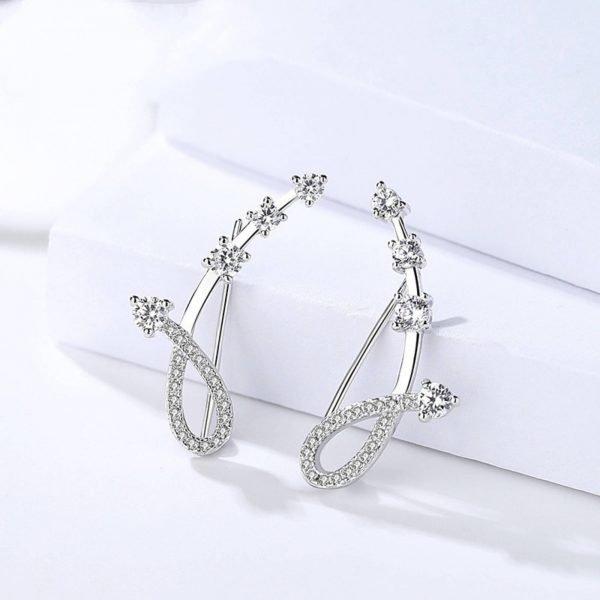 красиви сребърни обеци изкачващи се по ухото снимани под ъгъл