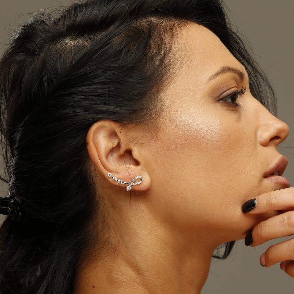 красиви сребърни обеци изкачващи се по ухото снимани на красив модел