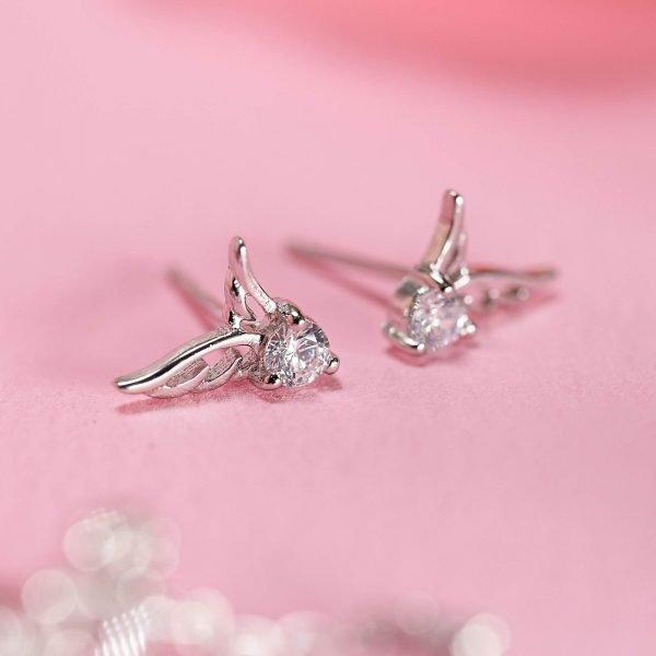 сребърни обеци с кубичен цирконий под формата на ангелски криле върху розова повърхност