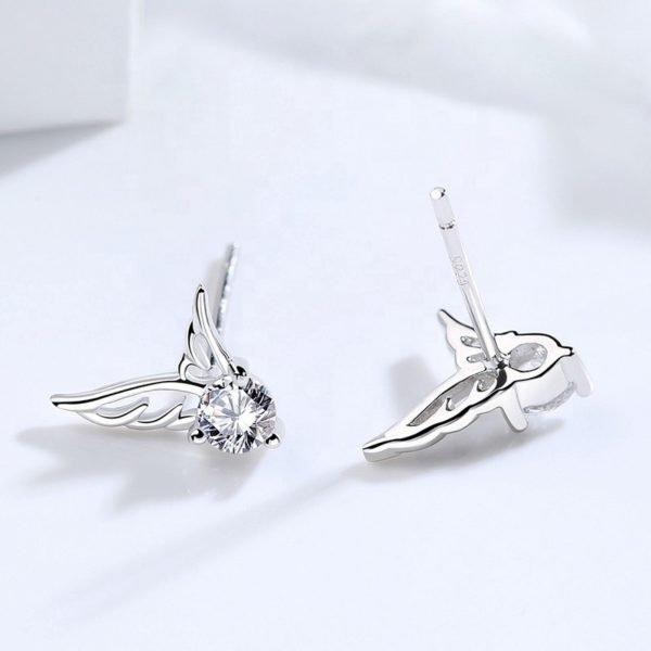 сребърни обеци с кубичен цирконий под формата на ангелски криле върху бяла повърхност