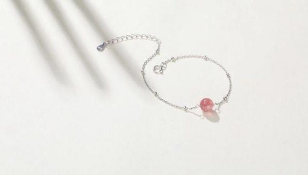 сребърна гривна с розов кристал под ъгъл на бял фон