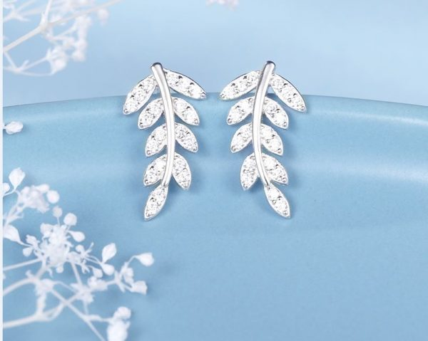 silver earrings in the shape of a leaf with cubic zirconia stones photographed on a blue background