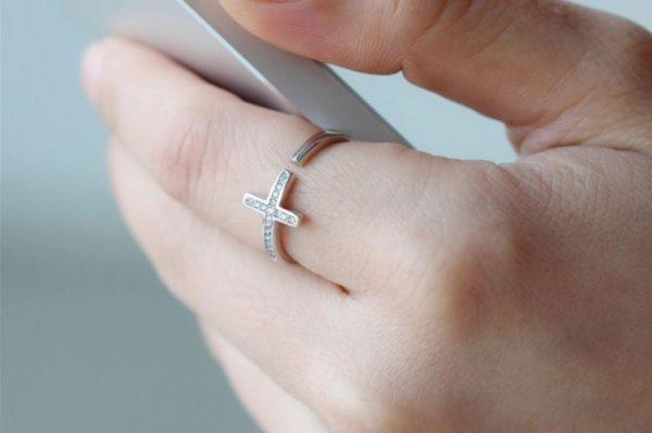сребърен саморегулиращ пръстен във формата на кръст на женска ръка държаща телефон айфон