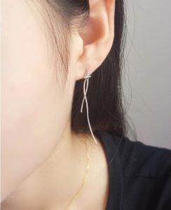 висящи сребърни обеци с кубичен цирконий за жена снимани на женско ухо