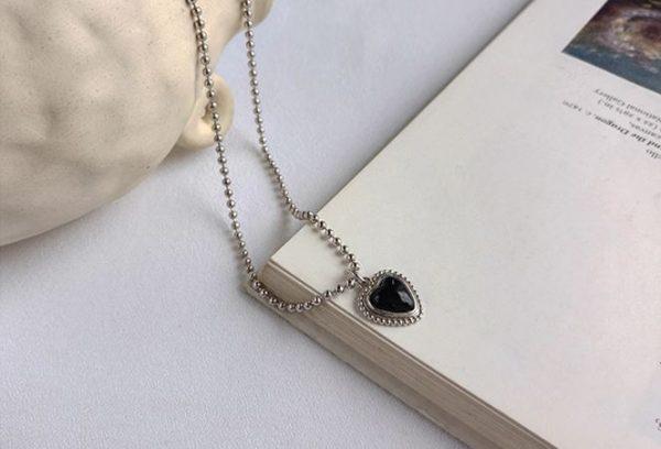 сребърно колие с черен оникс във формата на сърце под ъгъл върху книга