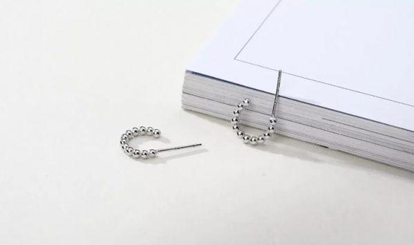 сребърни обеци с топчета пред книга снимани под ъгъл