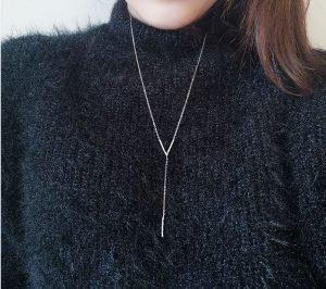 продълговато висящо сребърно колие от сребро 925 снимано на жена с черен пуловер