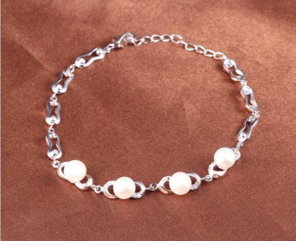 сребърна гривна с перли и кубичен цирконий снимана на кафяв фон