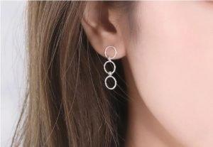 тройни висящи сребърни обеци във формата на кръгове снимани върху женско ухо