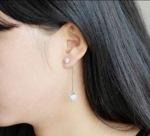 висяща сребърна обеца с камъни от кубичен цирконий снимана на женско ухо